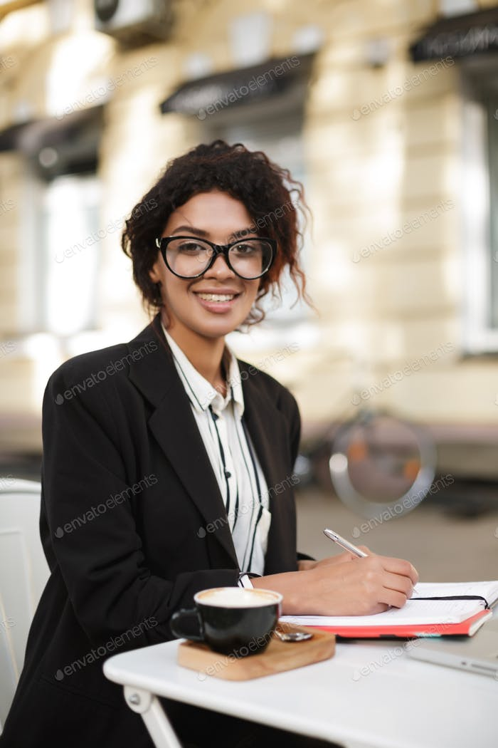 African American girl in glasses sitting at the cafe happily looking in camera with pen in hand