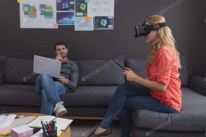 Side view of Caucasian business executives using multimedia devices on sofa in office