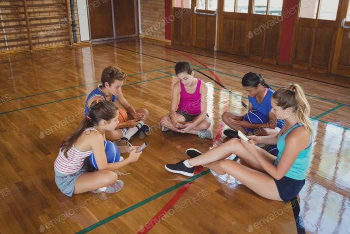 High school team using mobile phone while sitting in the basketball court