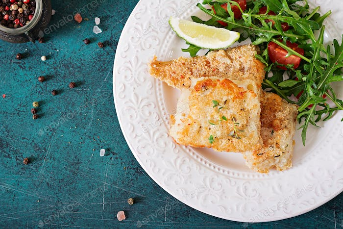 Fried white fish fillets and tomato salad with arugula. Top view
