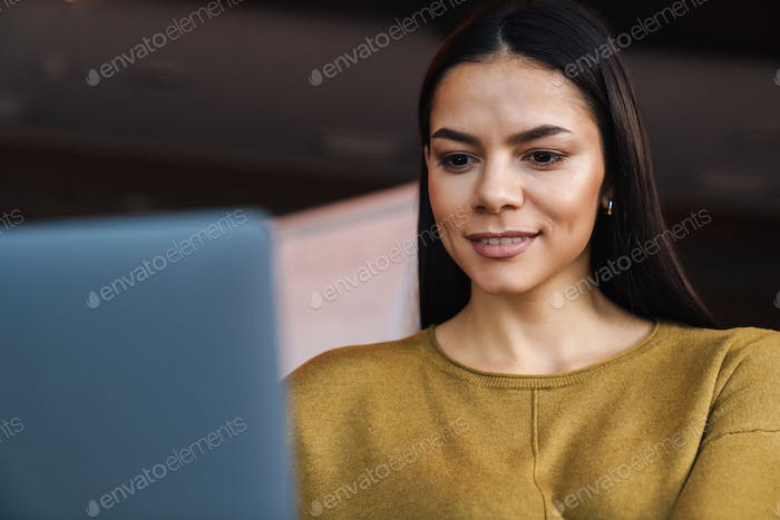 Image of young caucasian businesswoman working on laptop in office