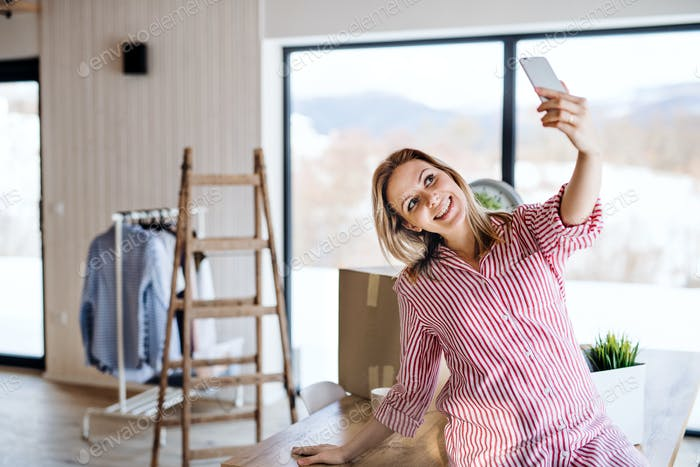 A young woman with smartphone moving in new home, taking selfie.
