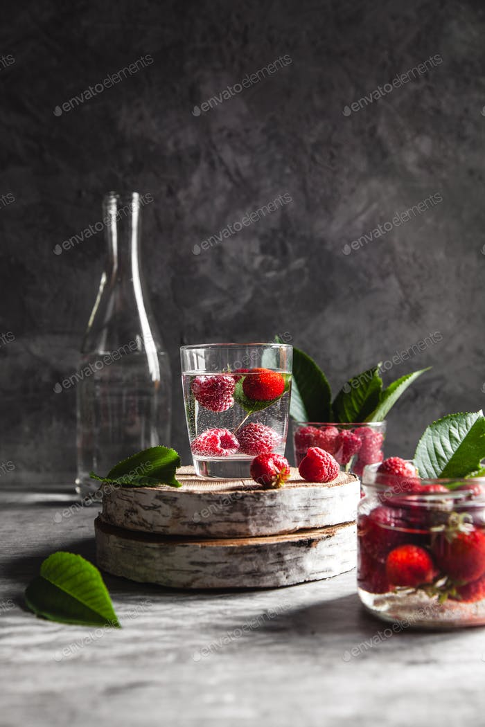 Strawberries in water on a dark gray background. Healthy food. A bouquet of flowers as decoration