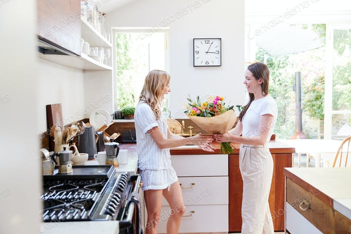 Woman Giving Gay Partner Bunch Of Flowers In Kitchen At Home