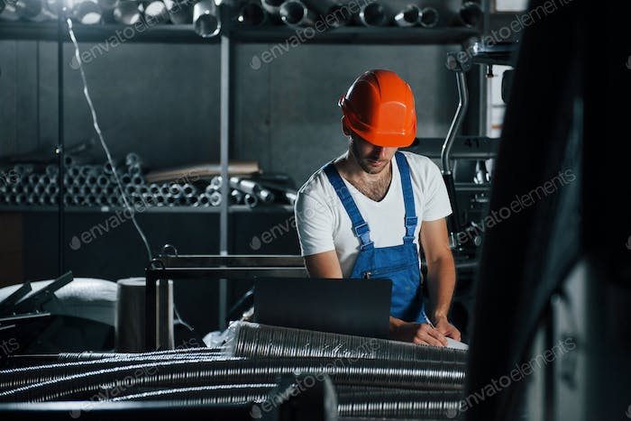 Front view. Man in uniform works on the production. Industrial modern technology
