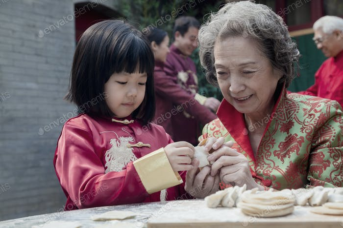 Grandmother and granddaughter making dumplings in traditional clothing