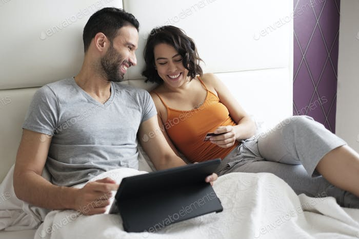 Happy Young Couple In Bed Buying Travel On Line