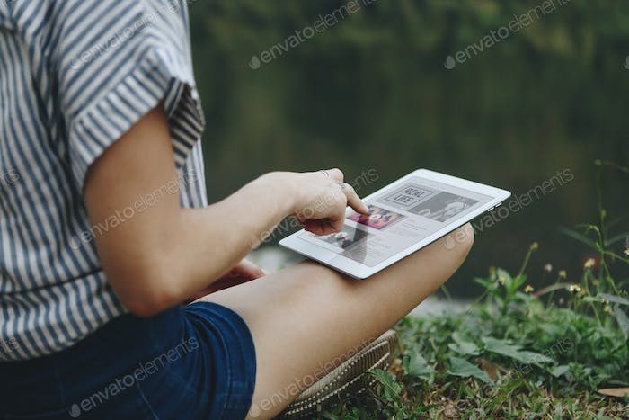 Woman alone in nature using a digital tablet with entertainment application on the screen