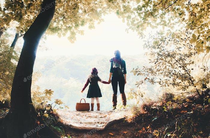Eine Rückansicht der Mutter mit einer Kleinkindtochter stehend im Wald im Herbst Natur.