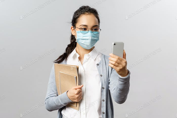 Covid19, virus, health and medicine concept. Young asian girl in medical mask, holding notebooks and