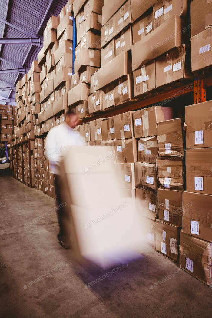 Blurred worker with fork pallet truck stacker with boxes in warehouse