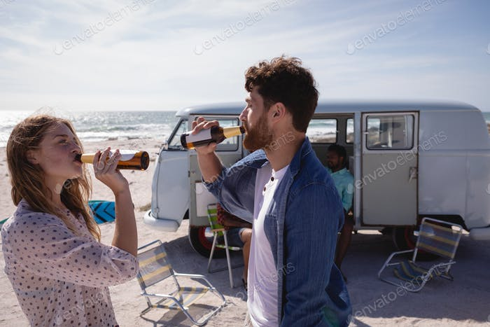 Diverse friends drinking beer on beach in the sunshine against a camper van