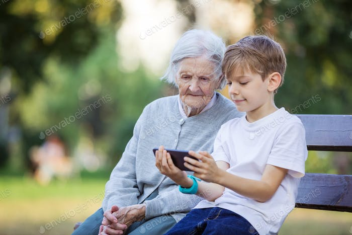 Young boy and his great grandmother watching video on smartphone.