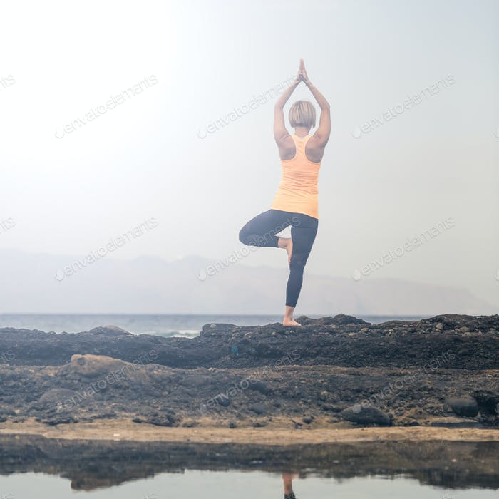 Chica de yoga meditando y Relajante en postura de yoga, vista al mar