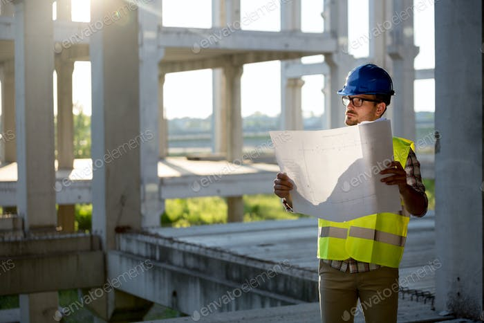 Engineer working on construction site and holding blueprint