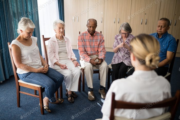 Senior people meditating with female doctor