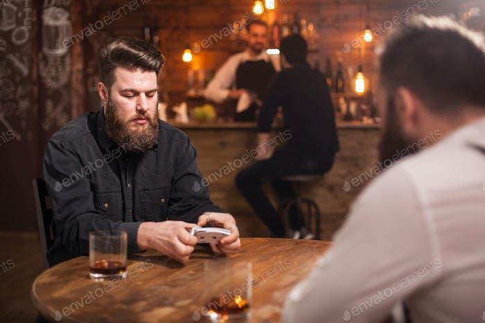 Zwei bärtige Hipster spielen ein Kartenspiel in einer Kneipe