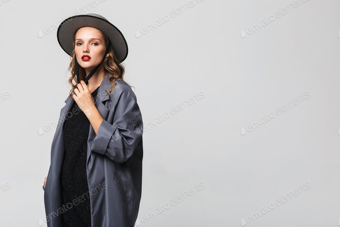 Fashion woman with wavy hair in modern hat and cloak posing over gray background. Copyspace