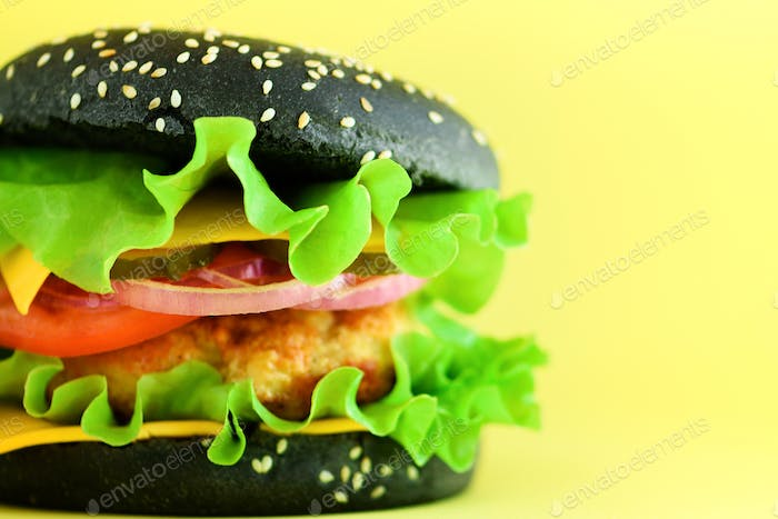 Macro view of tasty black burger with beef, cheese, lettuce, onion, tomatoes on yellow background