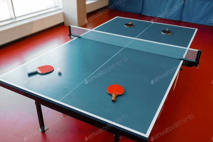 Ping pong rackets on game table with net, nobody