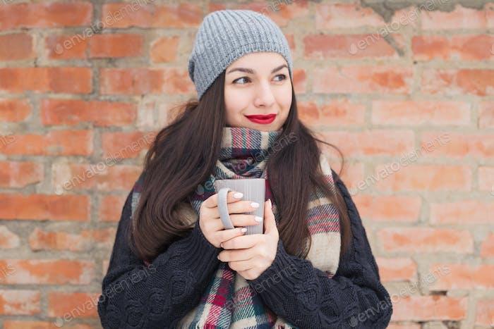 Hermosa Mujer Alegre sonriente con una taza en el invierno en la calle