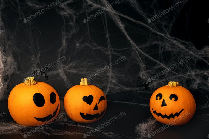 Little orange pumpkins with painted faces for Halloween