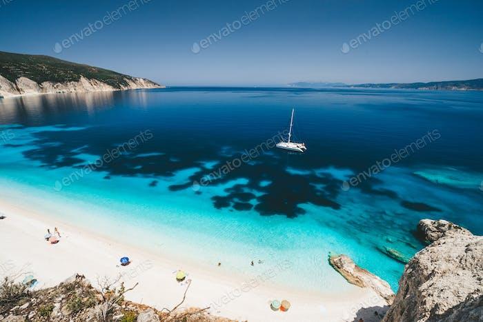 Пляжный отдых. Бухта Фтери, Кефалония, Греция. Белая яхта катамарана в прозрачной голубой морской воде