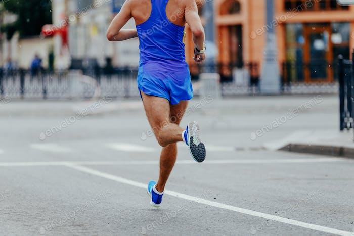 Rückenläufer-Athlet in blau Sportbekleidung Laufen Stadt im Regen
