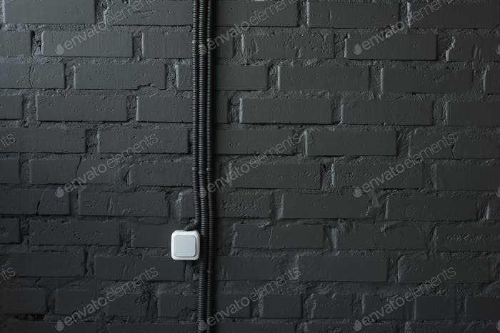 electrical switch and wires on black brick wall background