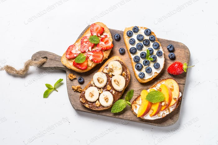 Sweet toast assortment with fresh fruit and berries on white