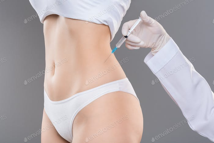 Young woman getting lipolysis treatment at plastic surgery clinic