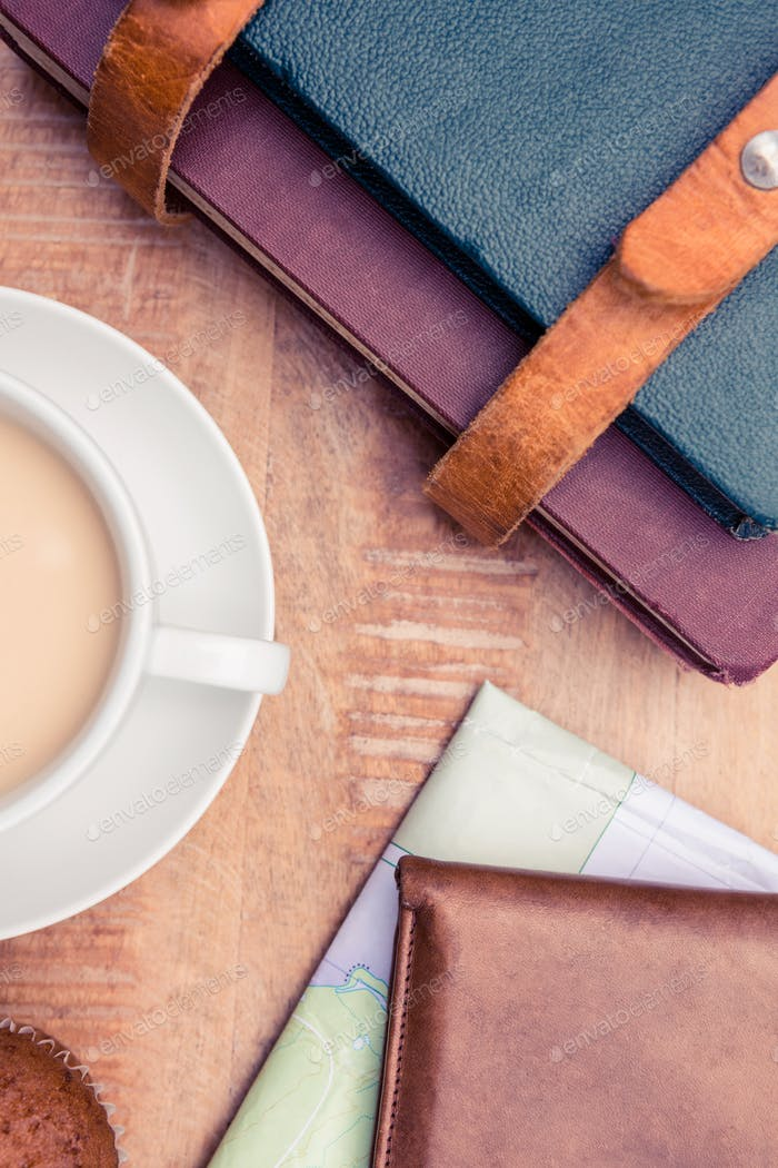 Close-up of coffee with wallet and diaries on table