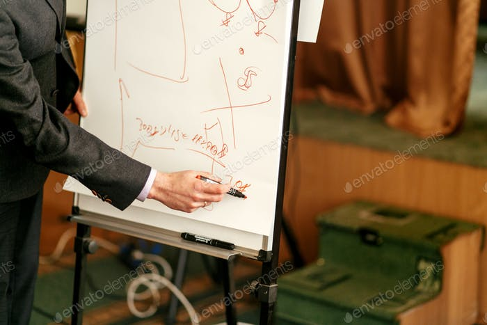 elegant speaker lecturer drawing charts at white board