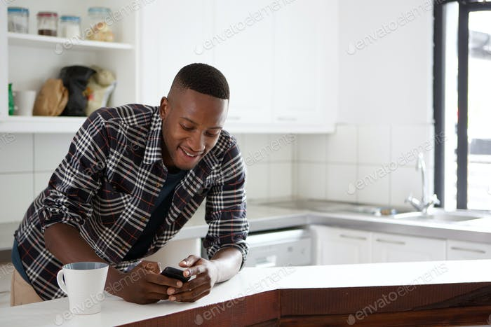 African man at the kitchen counter using mobile phone