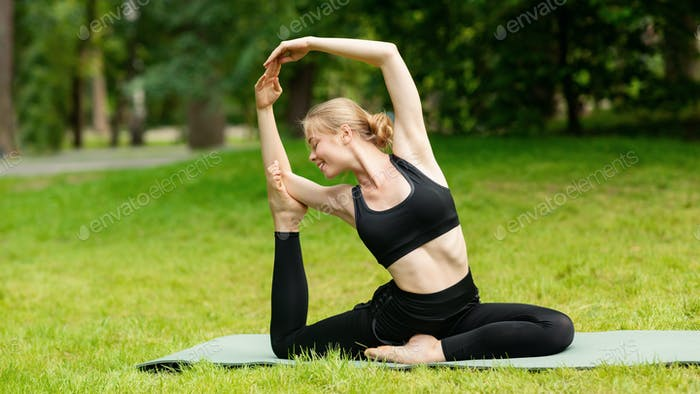 Flexible millennial woman doing complicated yoga asana on mat at city park
