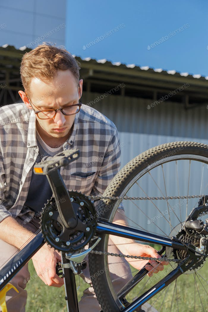 Young handsome man is tuning the bike chain.