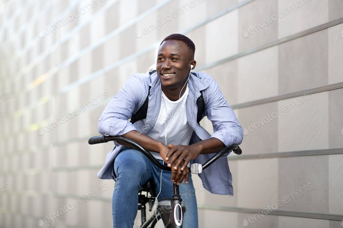 Handsome black guy with rucksack and earphones riding bicycle near brick wall downtown