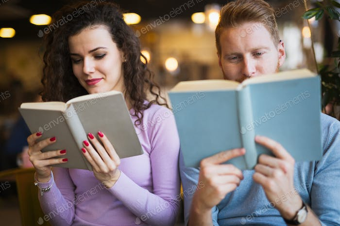 Young university students reading books