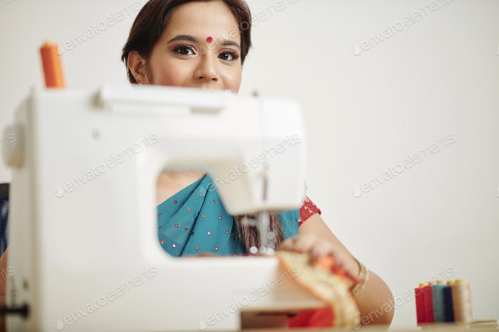 Cheerful woman sewing at home