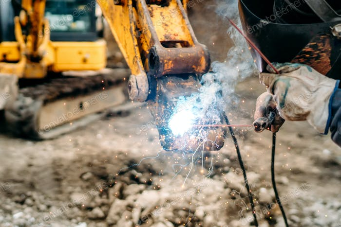 close up of welding details, sparks on construction site excavator