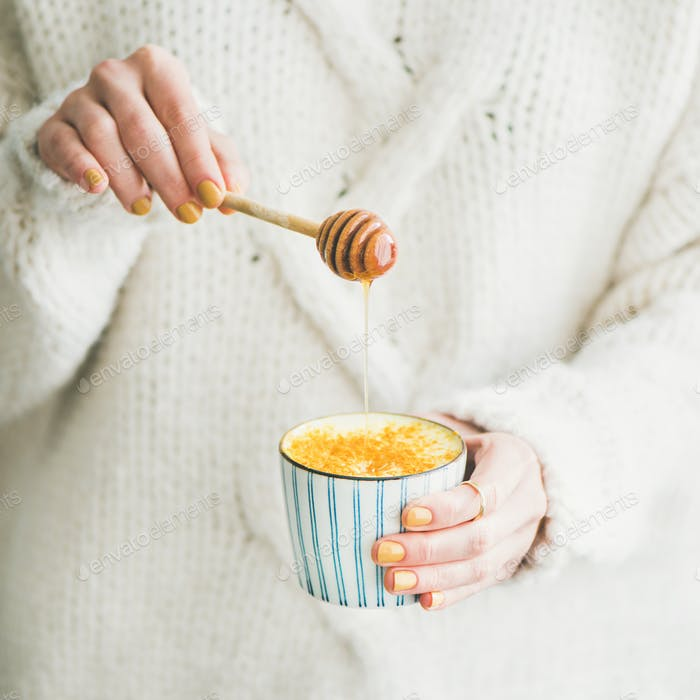 Healthy turmeric latte or golden milk with honey, square crop