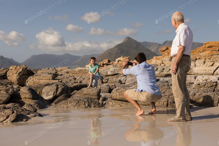 Father clicking photo of his son with mobile phone on beach in the sunshine