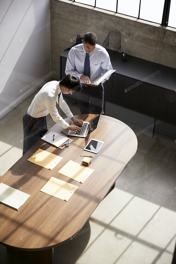 Two businessmen stand working at a desk in an office
