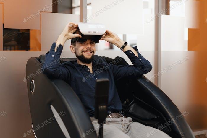 Ein Mann in einem Massage-Sessel mit VR-Technologie
