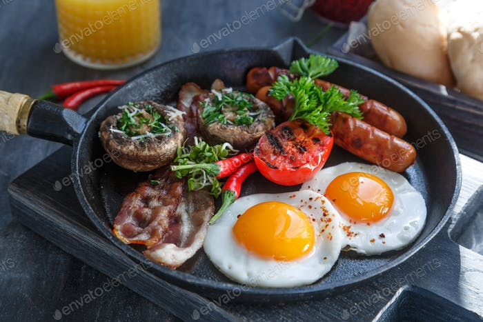 English Breakfast with fried eggs, sausages, bacon, mushrooms, jam and orange juice, copyspace