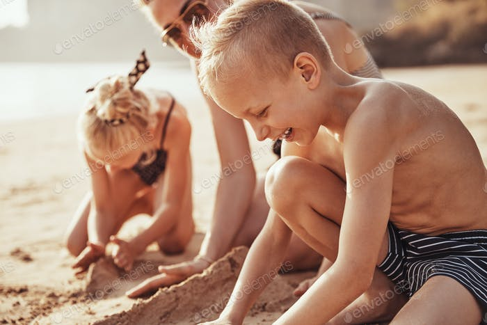 Cute little boy playing at the beach with his family