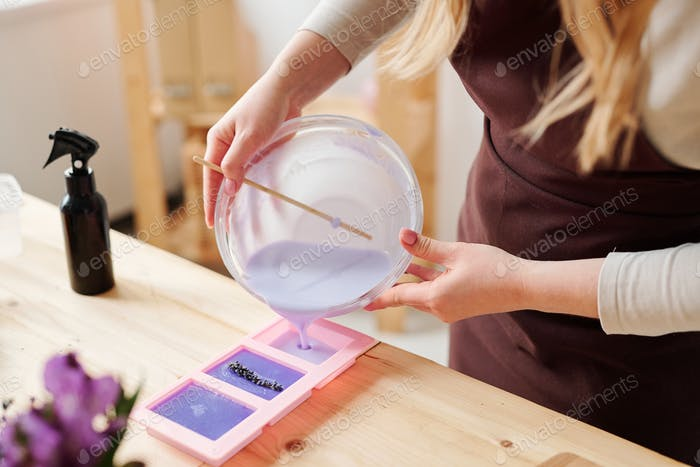 Hands of craftswoman in apron pouring lilac liquid soap mass into silicone molds
