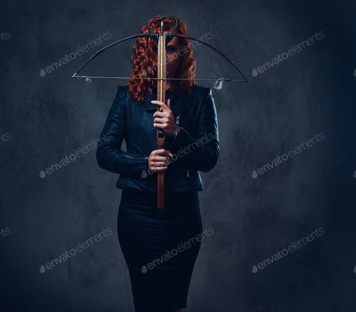 Redhead female  holds crossbow.