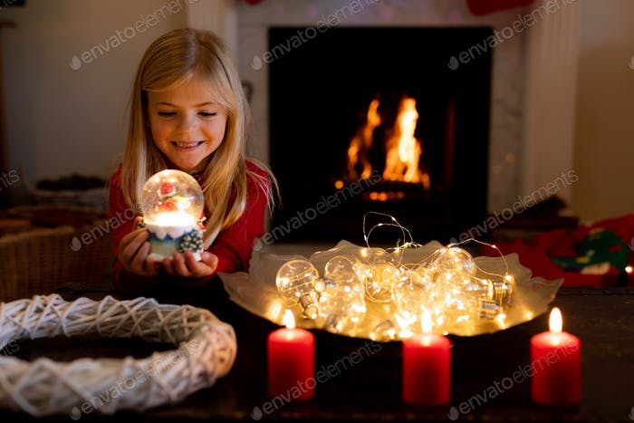 Young Caucasian girl holding a snow globe in the sitting room at Christmas time, smiling