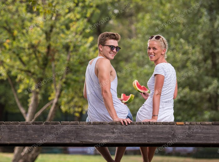 couple enjoying watermelon while sitting on the wooden bridge